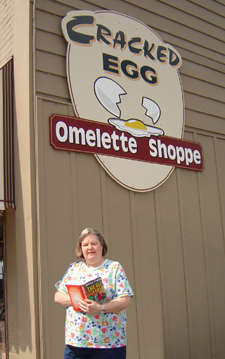 Vicki outside the omelette shop with a copy of Big Over Easy